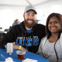 Two alumni smiling at camera at the tailgate